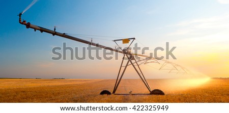Irrigation system on agricultural wheat field at summer sunset. - stock photo
