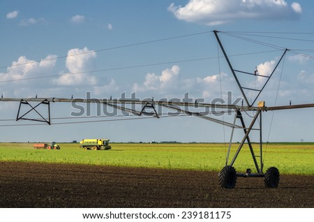 Irrigation system on the agricultural field and combine harvesting green peas on clear summer day. - stock photo