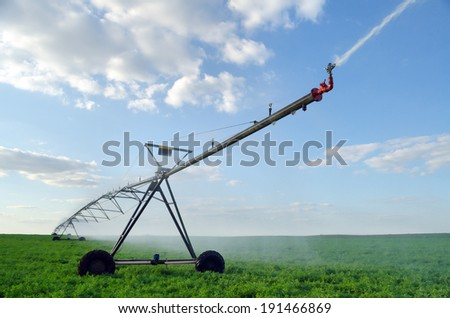 Irrigation system on the wheat field at summer sunrise. - stock photo