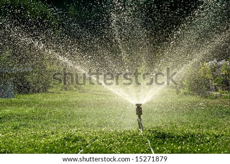 Irrigation system throwing water drops away - stock photo