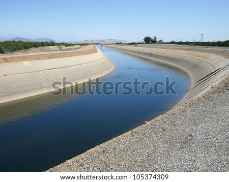 Irrigation water flows in a canal near an orange grove. - stock photo