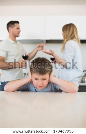 Irritated boy covering ears while parents arguing in background at home - stock photo