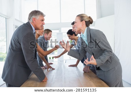 Irritated business team arguing in the office - stock photo