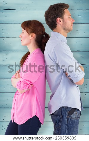 Irritated couple ignoring each other against wooden planks - stock photo