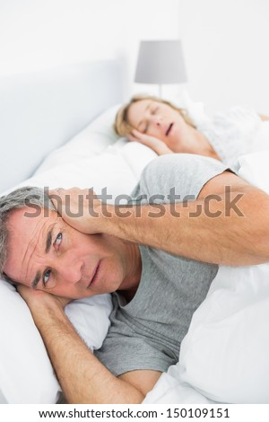 Irritated man blocking his ears from noise of wife snoring at home in bedroom