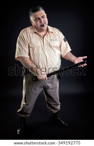 Irritated  security guard portrait, on a black background. Full length. - stock photo