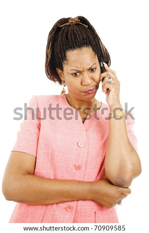 Irritated woman listening to a strange message on her cellphone.  Isolated on white. - stock photo