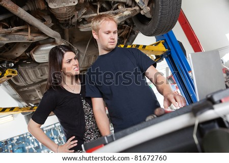Irritated young woman standing with mechanic using laptop in garage
