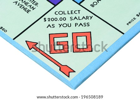 IRVINE, CA - MAY 27, 2014: Monopoly board game closeup of the Go corner. The classic real estate trading game from Parker Brothers was first introduced to America in 1935. - stock photo