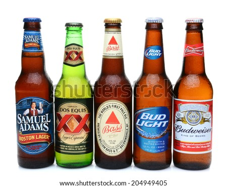 IRVINE, CALIFORNIA - JULY 14, 2014: 5 bottles of assorted cold beers. Domestic and Imported brews including, Budweiser, Bud Light, Bass, Dos Equis and Samuel Adams. - stock photo