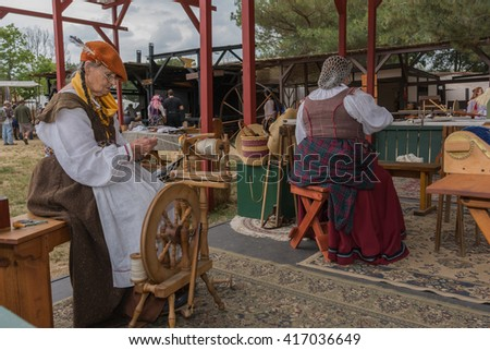 Irwindale, CA - USA - May 07, 2016: Women with medieval costumes working with fabric during The 54th Annual Renaissance Pleasure Faire.