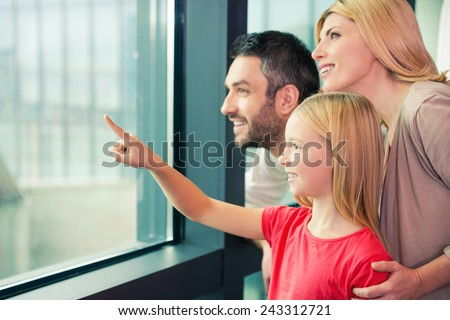 Is it a plane? Happy family of three bonding to each other and smiling while looking through a window together  - stock photo