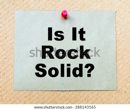 Is It Rock Solid? written on paper note pinned with red thumbtack on wooden board. Business conceptual Image - stock photo