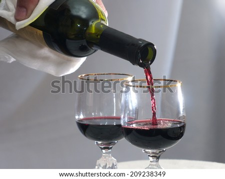 is poured into wine glass red wine, gray background - stock photo