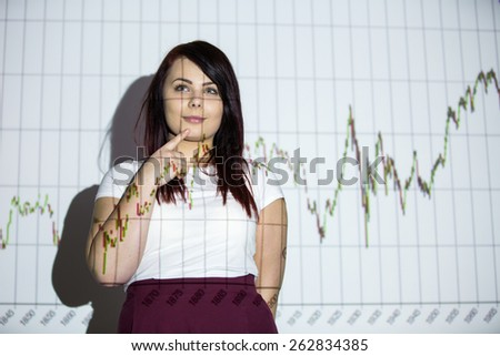 Is the market going to go up or down? To buy or to sell? - Young woman with a graph projection, thinking about her next step as an investor. Should she sell or buy? - stock photo