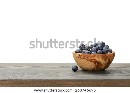 isabella grapes in wood bowl on table, border compostition - stock photo