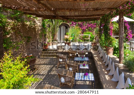 "ISCHIA ISLAND, ITALY - 08 JUNE 2012: The ""Castello"" restaurant open terrace with wooden roof and furniture. Ischia island, Gulf of Naples, Italy. - stock photo"