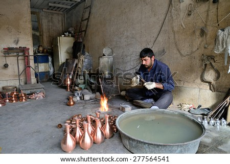 ISFAHAN - APRIL 18: Unknown man making traditional iranian souvenirs in a market (Isfahan Bazaar) in Isfahan, Iran on April 18, 2015. Bazaar is the most important tourist attraction in Isfahan, Iran. - stock photo