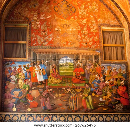 "ISFAHAN, IRAN - OCT 17: Dinner with belly dances in the king palace on the wall fresco in palace Chehel Sotoun on October 17, 2014. Safavid era ""Forty Columns"" palace was built in 1647 in Esfahan. - stock photo"