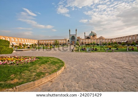 ISFAHAN, IRAN - OCT 17: People sitting and relaxing on the green grass of famouse Imam Square on October 17, 2014. Naqsh-e Jahan or Imam Square constructed in 1598. It is UNESCO's World Heritage Sites - stock photo