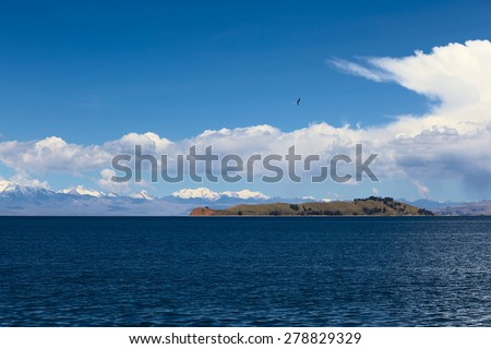 Isla de la Luna (Island of the Moon) in Lake Titicaca, Bolivia with the mountain range of the Andes in the back photographed from the popular tourist destination of Isla del Sol (Island of the Sun) - stock photo