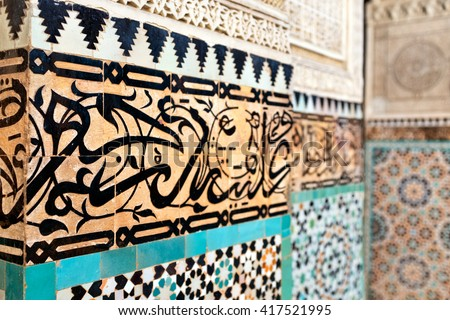 Islamic calligraphy detail. Traditional Arabic Coranic Calligraphy in the madrasa Bou Inania, Meknes, Morocco - stock photo