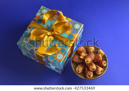 Islamic Festive Gift and dates. Bowl of Arabian dates with gift pack on blue background. - stock photo