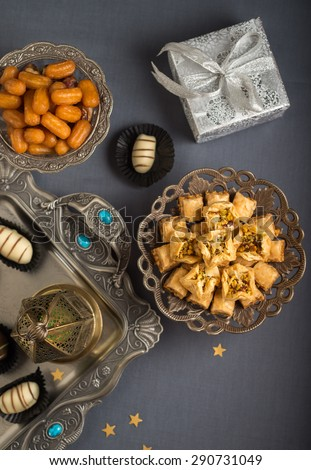 Islamic festive still life. Eid is celebrated with special sweets and distributing gifts. Studio shot from the top. - stock photo