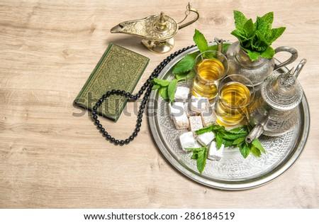 Islamic holidays decoration. Ramadan kareem. Tea glasses and pot, arabian lantern, holy book quran and rosary. Oriental hospitality concept - stock photo