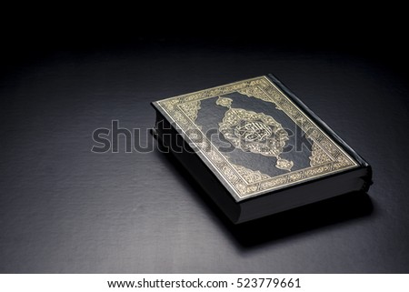 Islamic Holy Book Quran Under Soft Light on Black Background