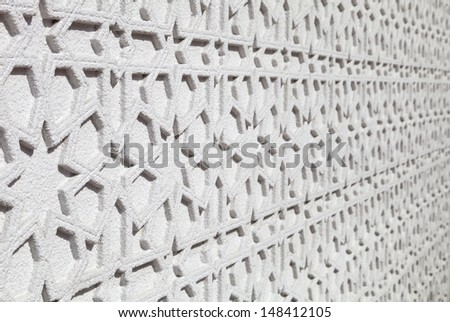 Islamic pattern with stars on white wall - stock photo