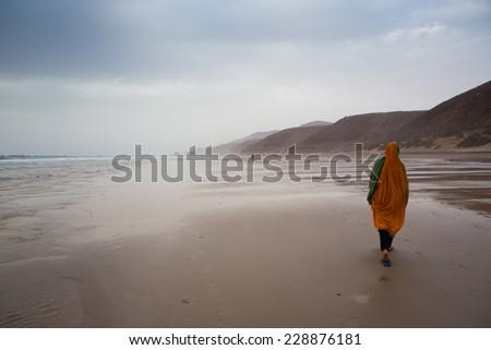 Islamic women walking on the beach in Legzira Beach under a cloudy sky. - stock photo