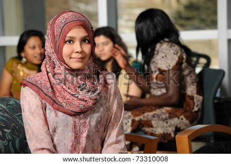 Islamic Young woman with diverse group of female students dressed in traditional clothing inside school setting - stock photo