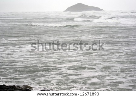 Island barely visible through the waves and gusts of an ocean storm on the pacific - stock photo