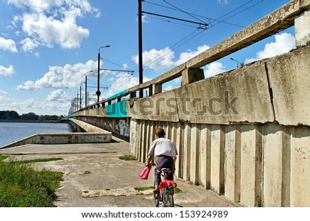 Island bridge with cyclist in Riga. - stock photo