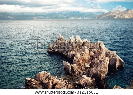 Island cliffs and seascape, aerial view with calm sea and clear sky. Soft, vintage effect on photo - stock photo