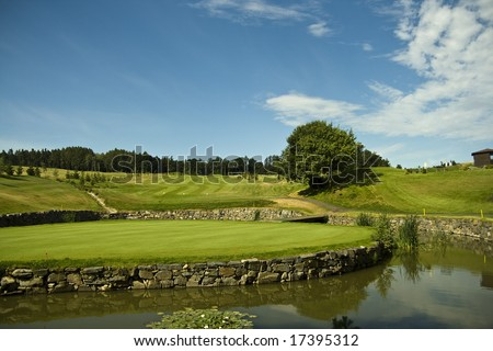 island green of a beautiful golf course with dramatic summer sky - stock photo
