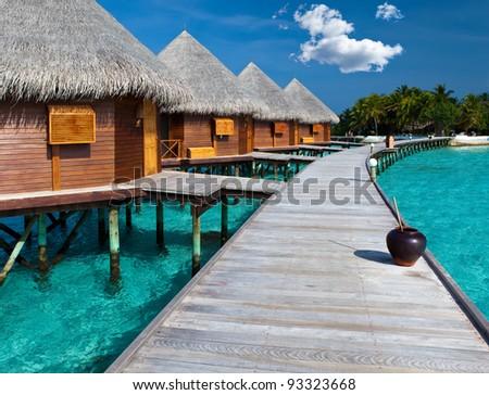 Island in ocean, Maldives.  Villa on piles on water - stock photo