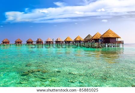 Island in ocean, overwater villas - stock photo