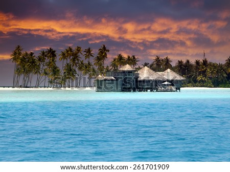 Island in ocean, overwater villas at the time sunset - stock photo