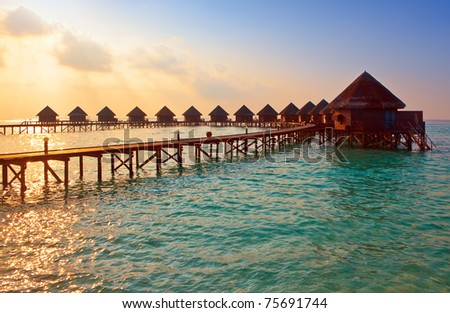 Island in ocean, overwater villas at the time sunset. - stock photo