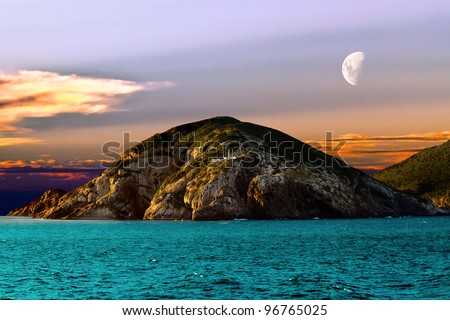 Island of Cabo Frio in the state of Rio De Janeiro, Brazil. View from a cruise ship cruising through Atlantic Ocean. In the center of the island there is a lighthouse and the moon is on the sky. - stock photo
