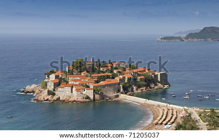 Island of Sveti Stefan at the Adriatic coast in Montenegro. It's red roofed old houses were used by pirates, now as a hotel resort. - stock photo
