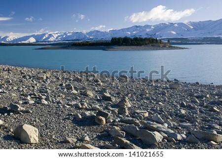 Island on Lake Pukaki, glacier water, low lake level, New Zealand - stock photo