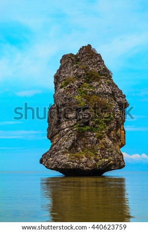"Island ""Sail"" in the ocean. The blue haze of the warm sea - background for the huge stone cliff. The island is reflected in the smooth surface of the water"