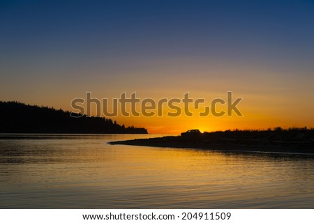 Island Sunset. A man in an automobile parks along the shoreline to view the summer setting sun in the San Juan Islands of western Washington State. - stock photo