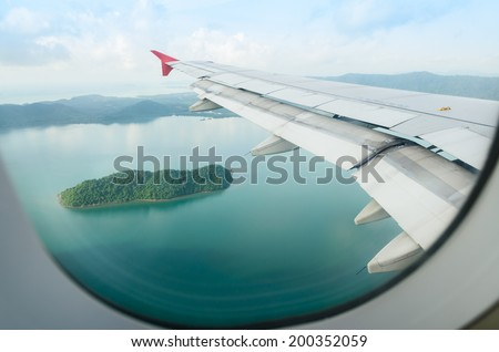 island view through aircraft windows over the sea - stock photo