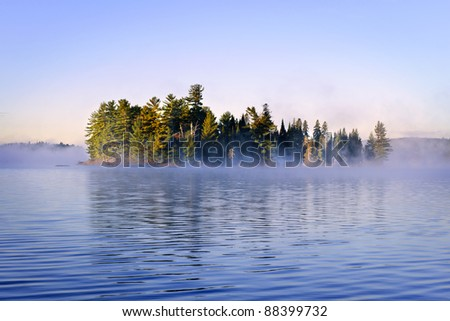 Island with pine trees in morning fog on lake at sunrise - stock photo