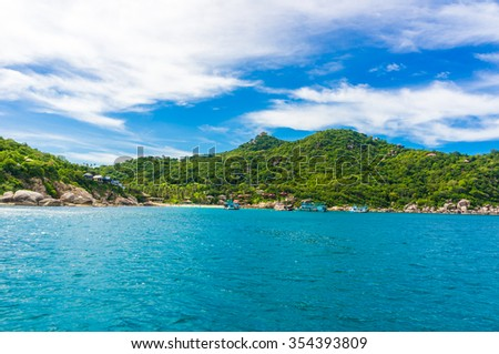 Island with Turquoise Water and Green Palm Trees on a Tropical rock Island - stock photo