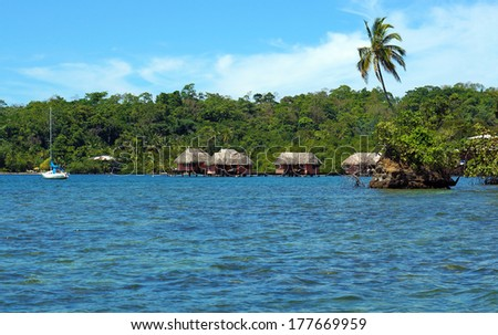 Islet with coconut tree and in background thatched cabins over the water, Caribbean sea, Bocas del Toro, Panama - stock photo